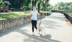Blonde lady walking outside with medical mask on face with her golden retriever near a lake
